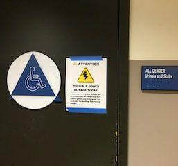 Photo of all gender restroom signage in AC building.